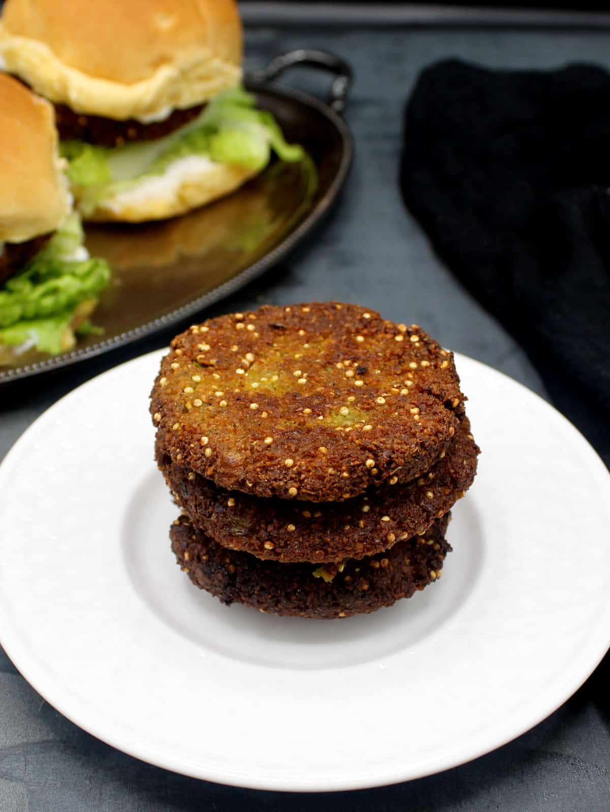 Photo of three stacked falafel burger patties with burgers in the background.