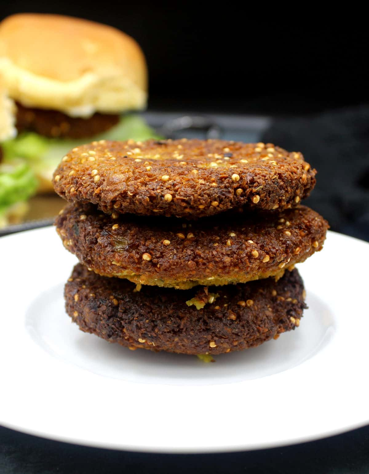 Photo of a stack of three falafel burger patties.