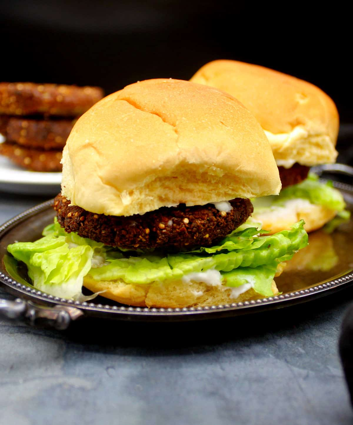 Front closeup photo of a falafel burger with lettuce, mayo and burger patty.