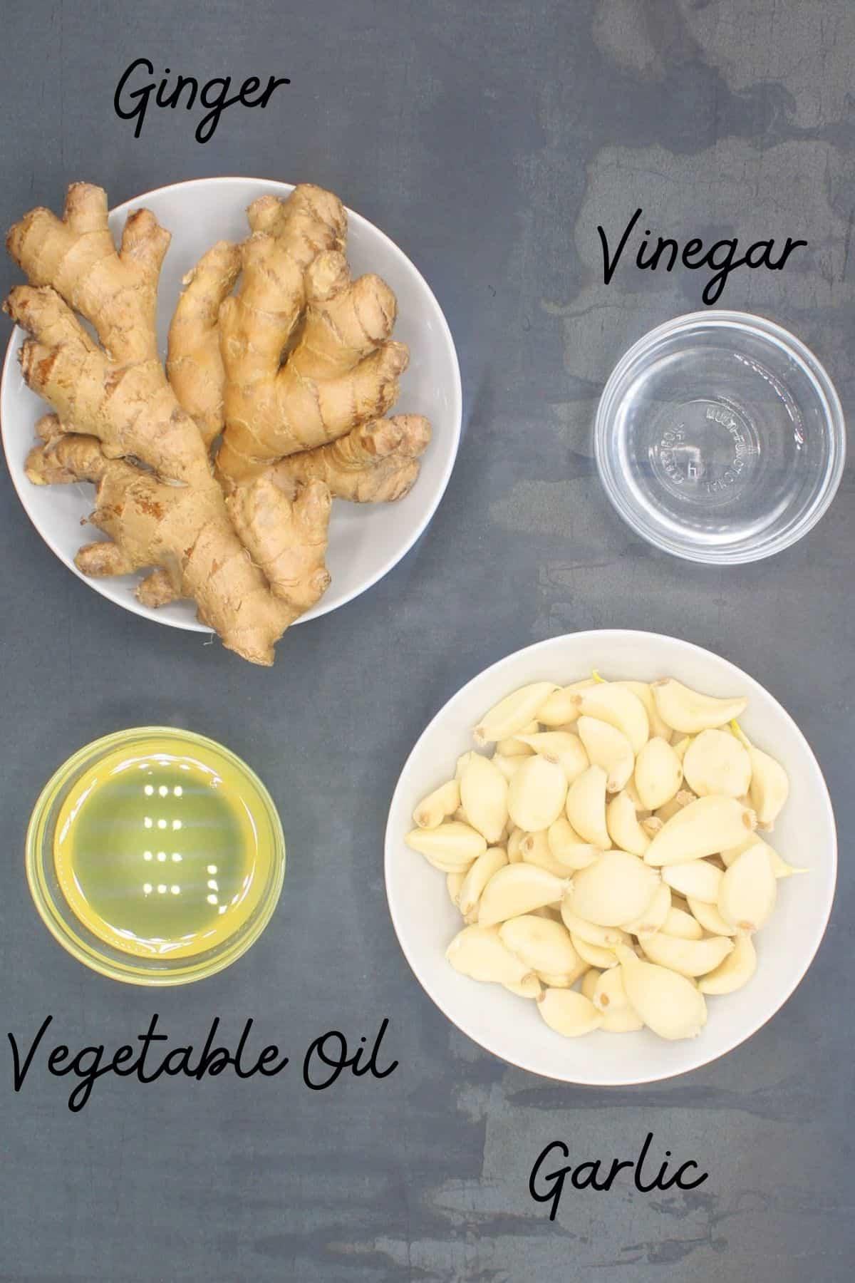 Photo showing ingredients used to make ginger garlic paste, including gingerroot, garlic, vegetable oil and vinegar.