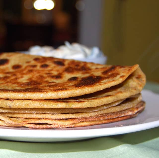 Photo of gobi parathas stacked on a white plate.