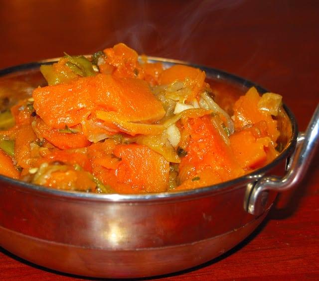 Photo of velvety herbed pumpkin in a steel kadhai serving bowl.
