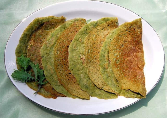 Photo of a row of kale dosas on a white oval plate.