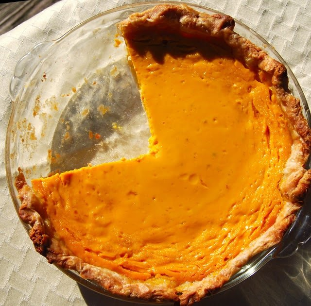 Photo of vegan mango pie with a couple of slices removed in glass baking dish.