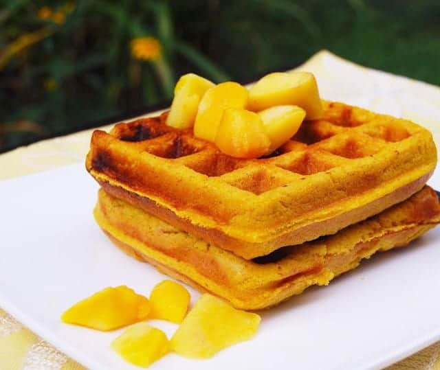 Photo of gluten-free vegan mango waffles with mango chunks on a white plate.
