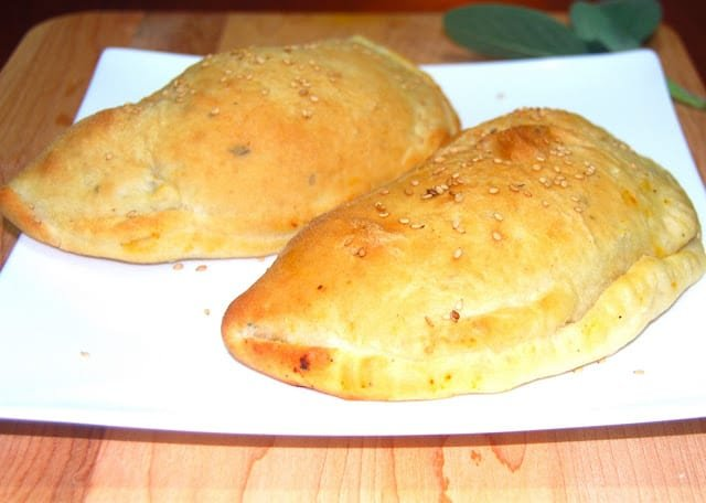 Photo of two kheema-stuffed naan calzones on a white plate.