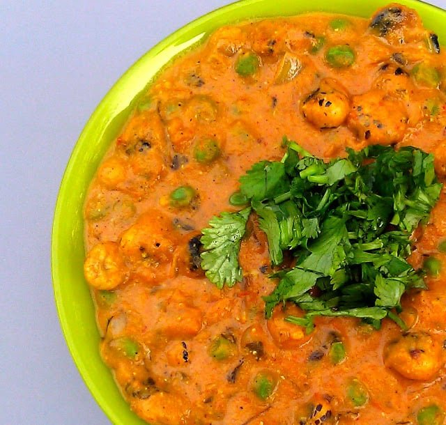 Photo of phool makhana curry in a green bowl with a cilantro garnish.