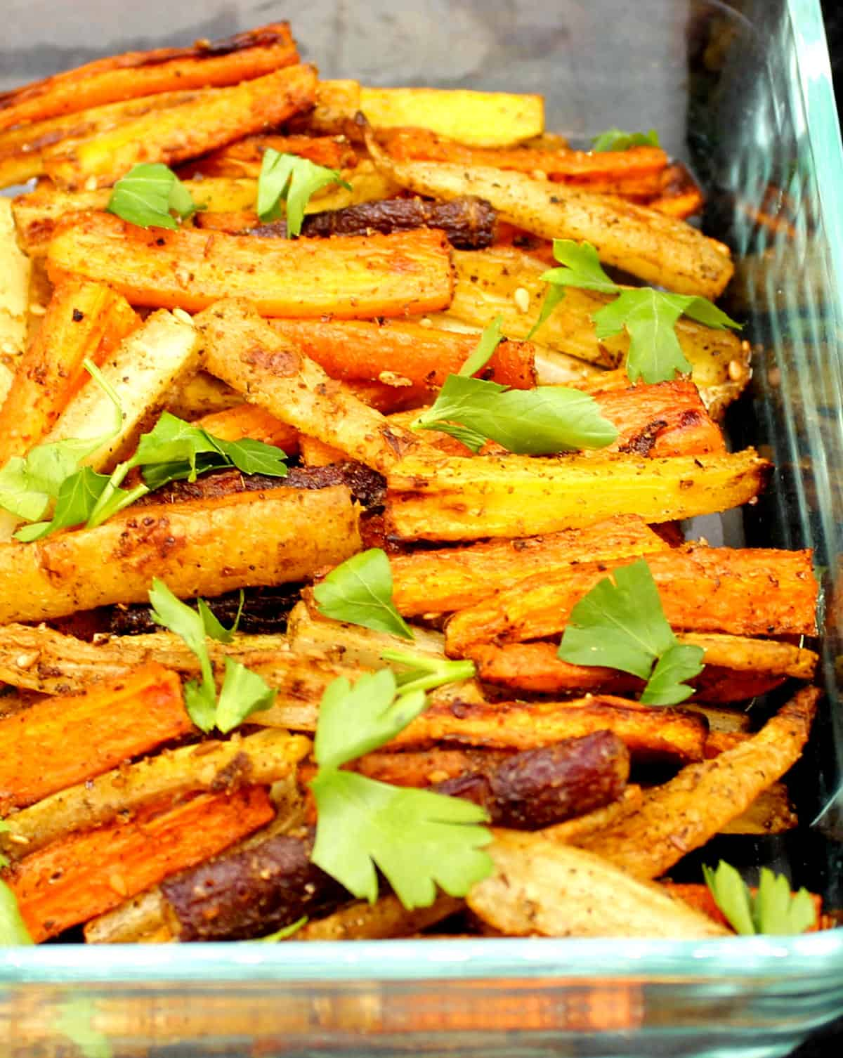 Closeup of roasted carrots with zaatar in a glass baking dish with parsley garnish.