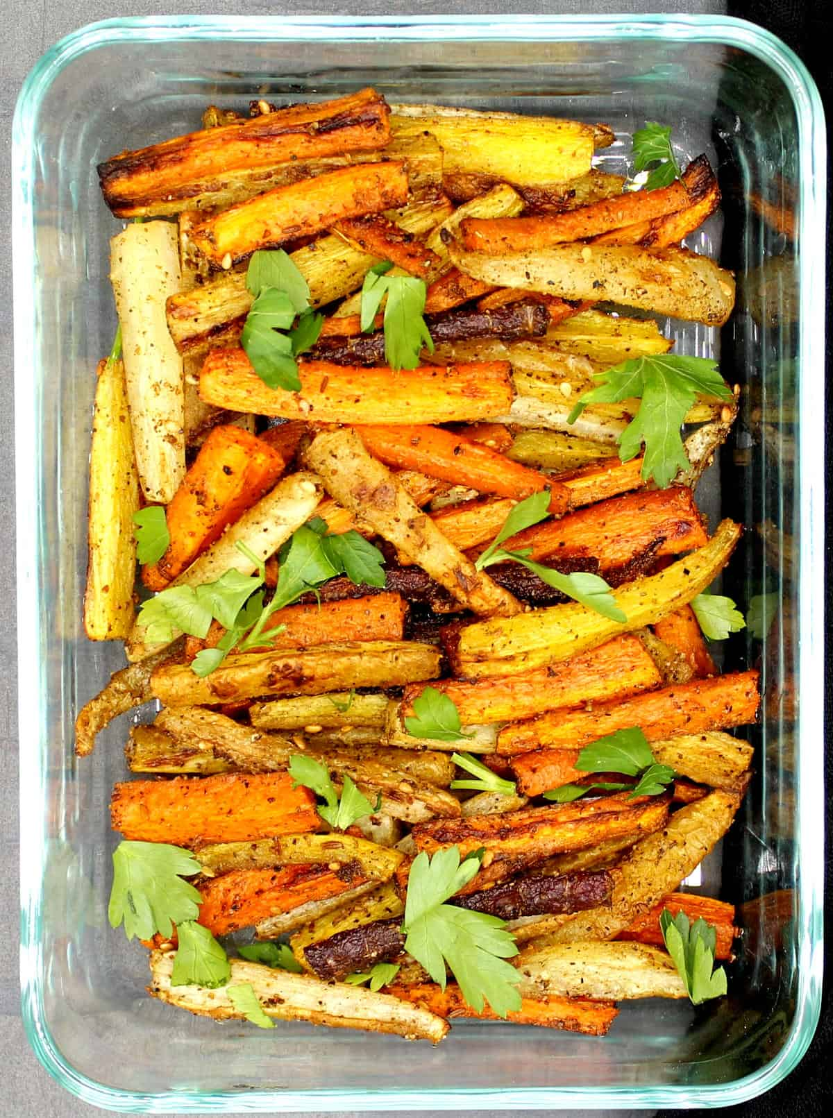 Multicolored roasted carrots with zaatar in a glass baking dish with parsley on top.