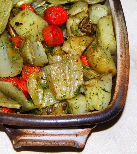 Photo of roasted vegetables with fennel vinaigrette in a brown bowl.