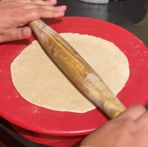 Sourdough roti being rolled out on a red rolling board with a wooden rolling pin