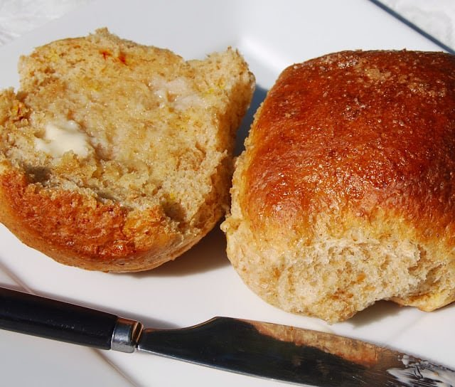 Photo of the buttered crumb of a saffron bun on a plate.