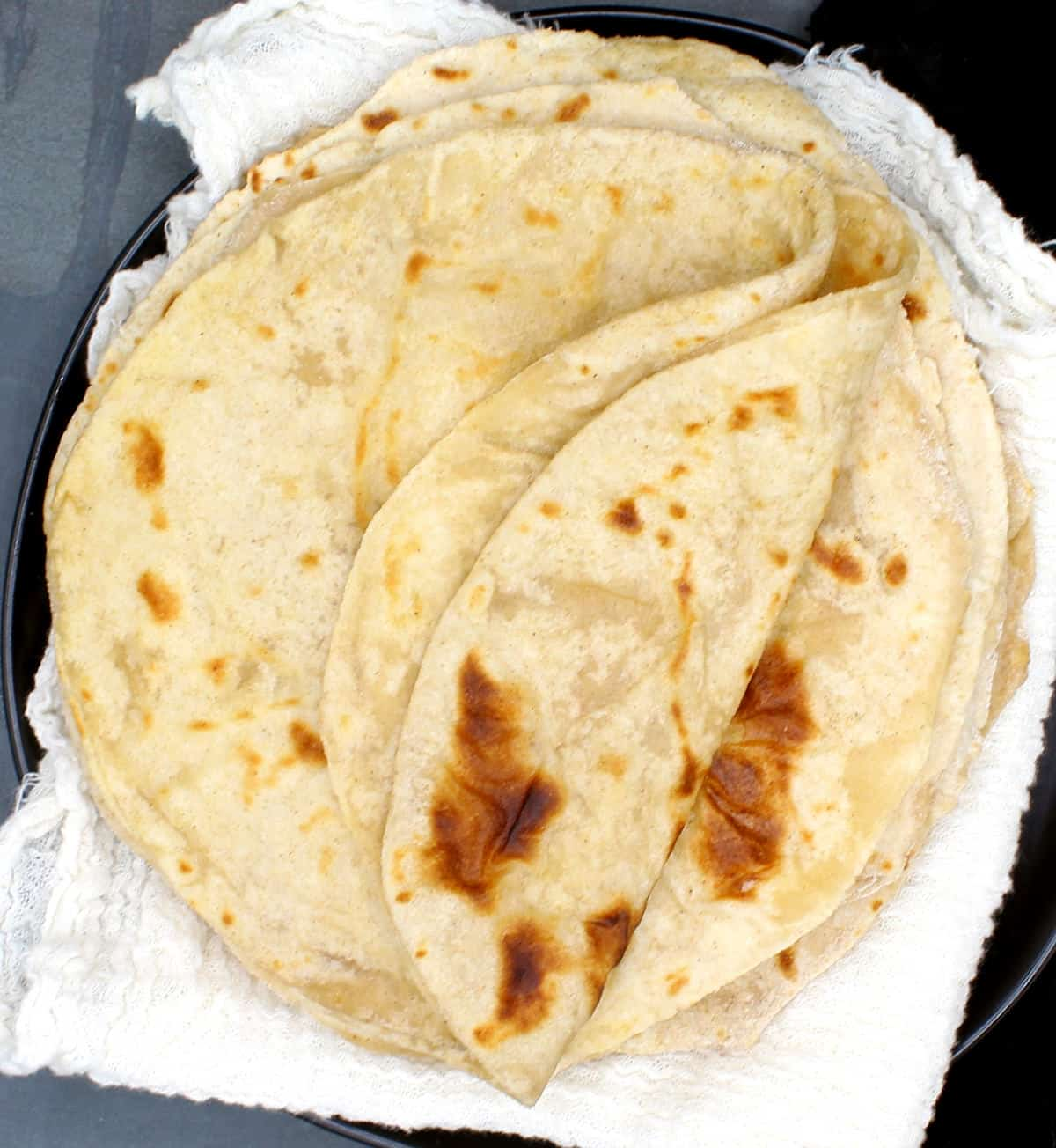 Photo of a stack of soft, pliable, perfect rotis made with sourdough starter on cheesecloth on a black plate.