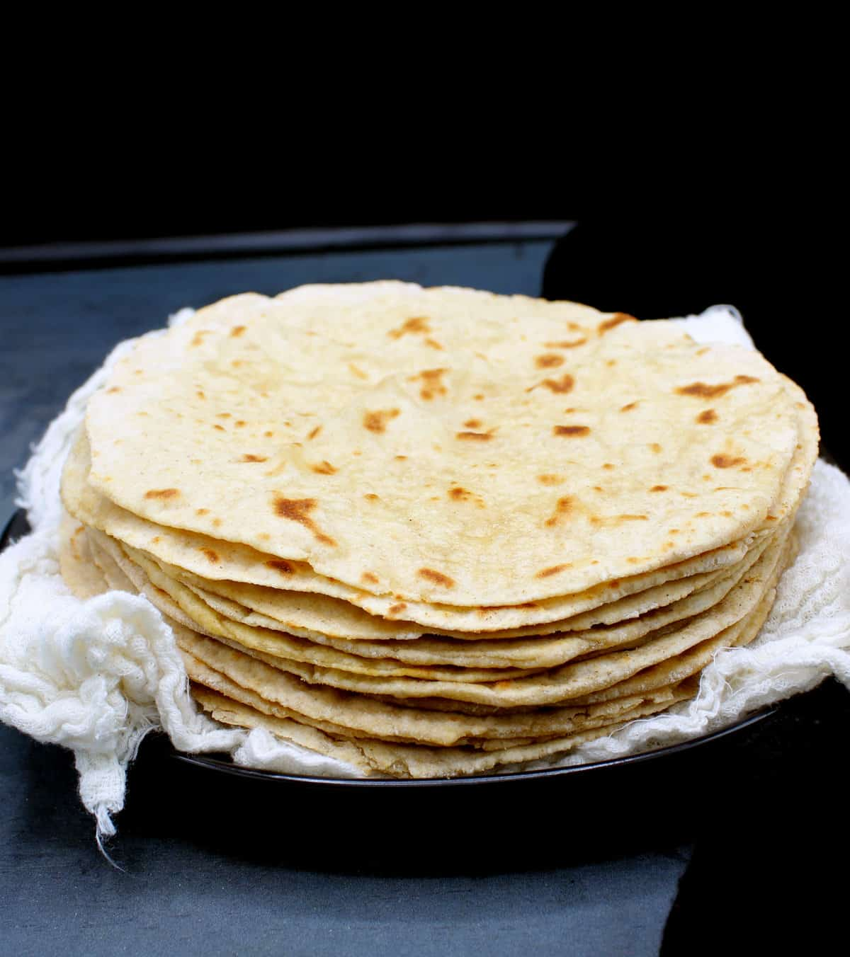 Photo of a stack of soft sourdough rotis wrapped in cheesecloth on a black plate.