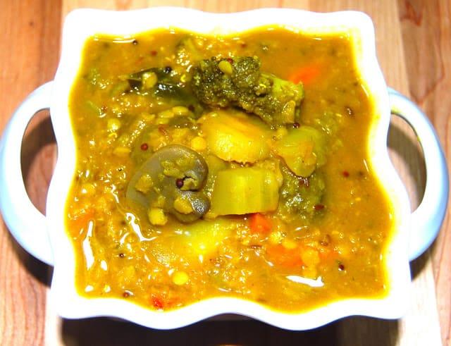 A square ceramic bowl with stir-fry veggie sambar