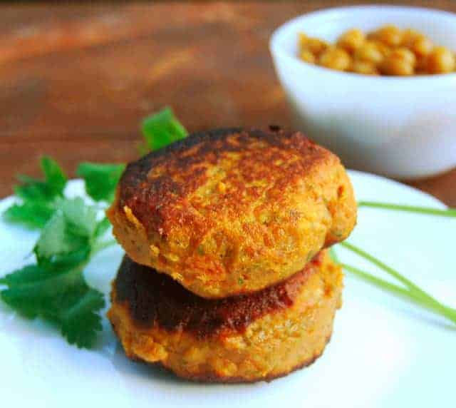 Photo of sweet potato patties stacked on a white plate with cilantro and the chickpea sauce in background.