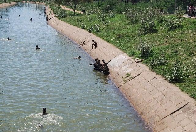 Photo of kids swimming in a canal near Madurai