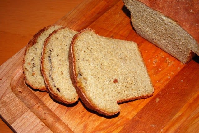 Photo of a sliced loaf of whole wheat vanilla bread on a chopping board.