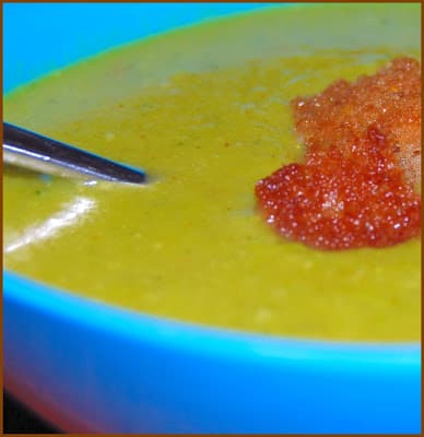Photo of vegan broccoli potato soup with golden baked croutons in a blue bowl with a spoon.