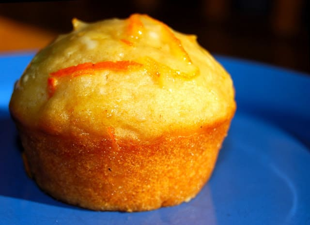 Photo of vegan coconut muffin with orange glaze on blue plate.