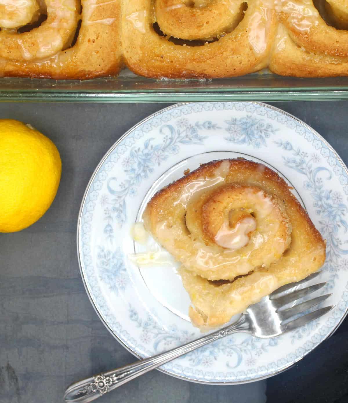 An overhead shot of a perfect golden vegan lemon roll glazed with a sticky lemon glaze with bits of lemon zest.