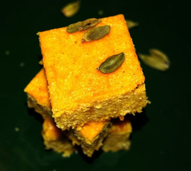 A photo of a stack of sweet vegan mango cornbread with cardamom pods scattered around.