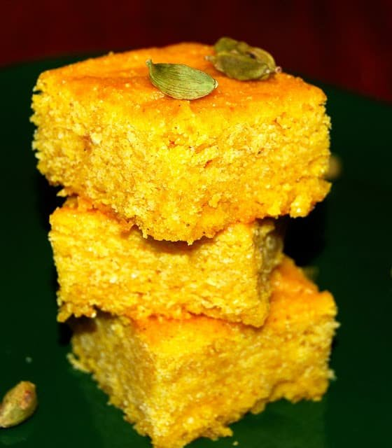 A photo of a stack of vegan mango cornbread squares with cardamom pods.