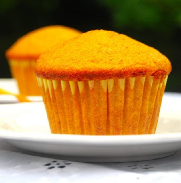 Photo of a bright orange vegan mango muffin on white plate with another muffin in the background.