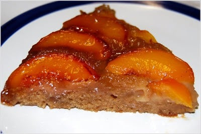 Photo of a slice of vegan peach upside down cake on a plate.