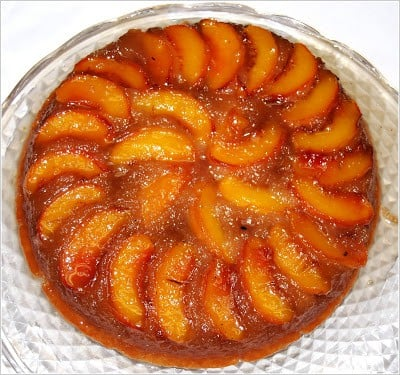 Photo of Vegan Peach Upside Down Cake on a glass cake stand.