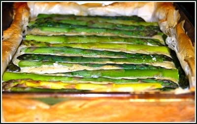 Photo of a creamy vegan asparagus and potato tart with asparagus spears layered on a creamy white filling encased in filo sheets.