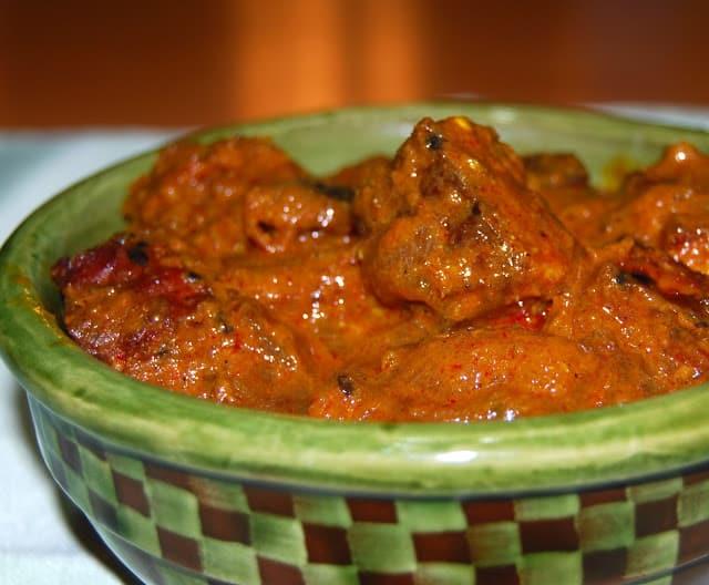 Photo of Kashmiri rogan josh in a green and brown bowl.