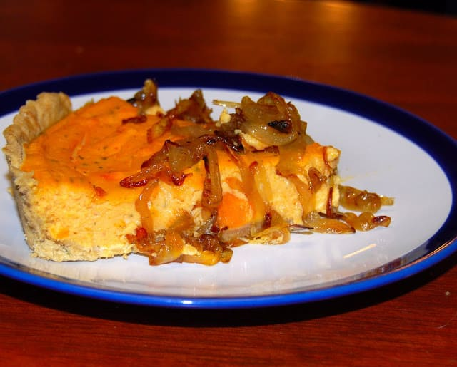 Photo of a slice of vegan sweet potato quiche topped with caramelized onions.
