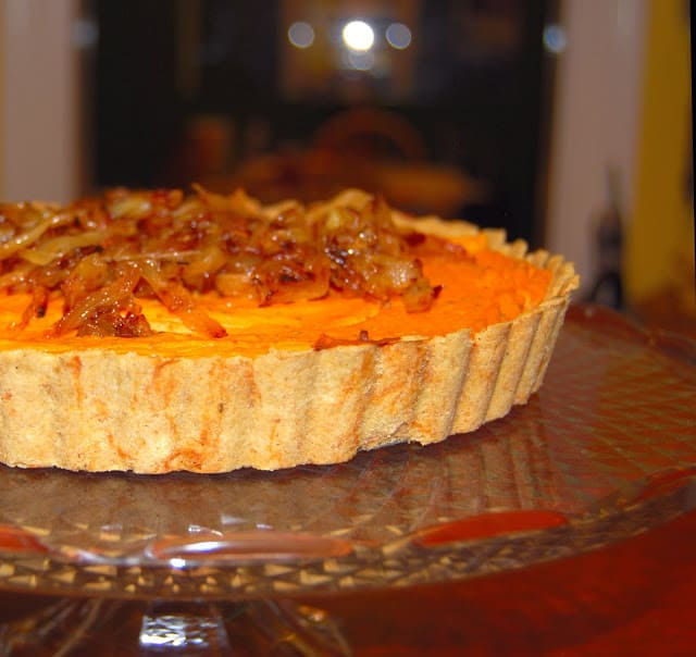 Photo of vegan sweet potato quiche on a glass stand.