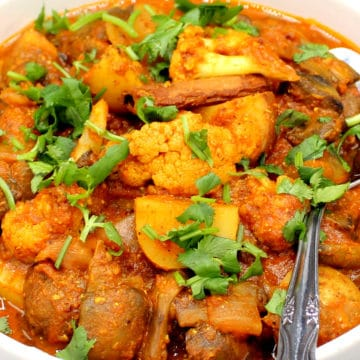 A photo of vegetable vindaloo with potatoes, cauliflower and mushrooms in a white bowl with a spoon