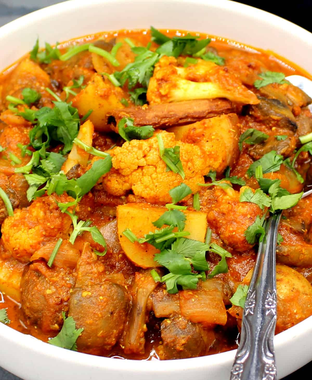 Close up photo of a bowl of appetizingly red vegetable vindaloo with cauliflower, mushrooms and potatoes and a cinnamon stick.