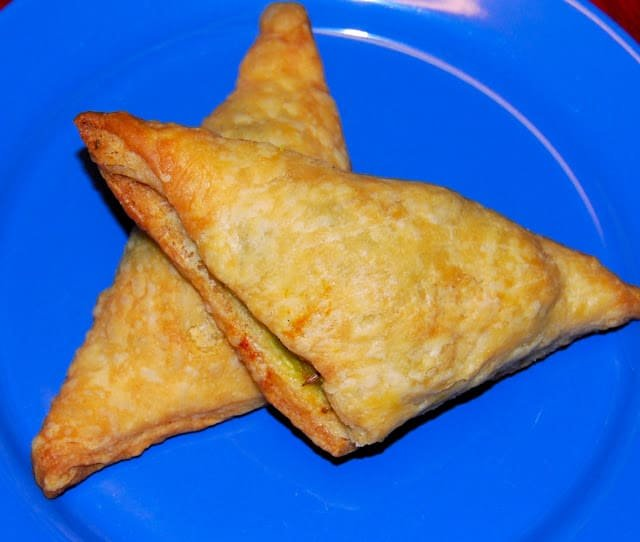 Photo of two golden vegetable puffs on a blue plate.
