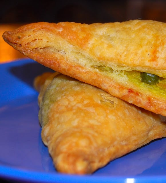Closeup photo of two vegetable puffs on a blue plate.