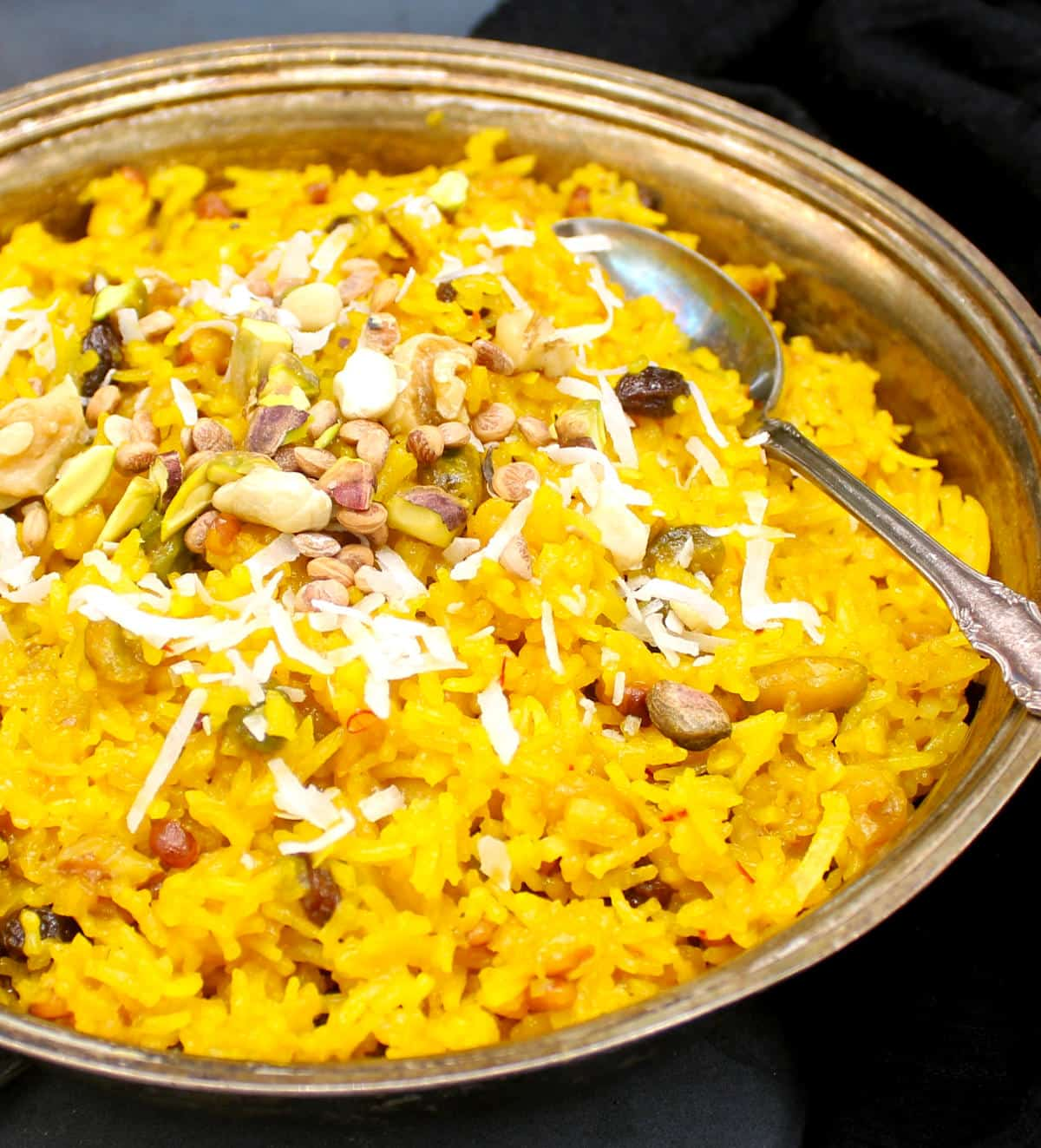 Photo of zarda pulao in a silver serving dish with nuts and dry fruits and shredded coconut.