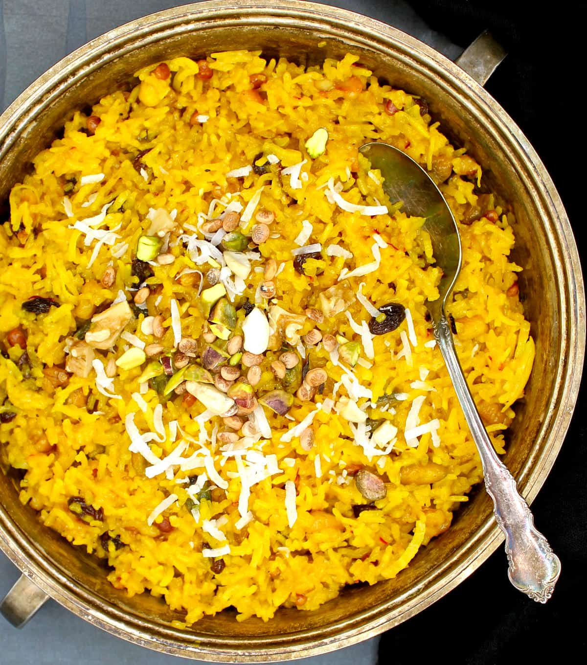 Overhead photo of a silver server with vegan zarda pulao with fruits and nuts and a silver spoon.