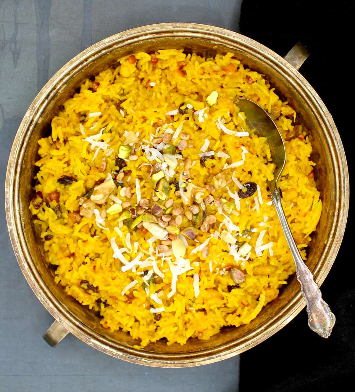 Photo of vegan zarda in a silver serving dish with a spoon.