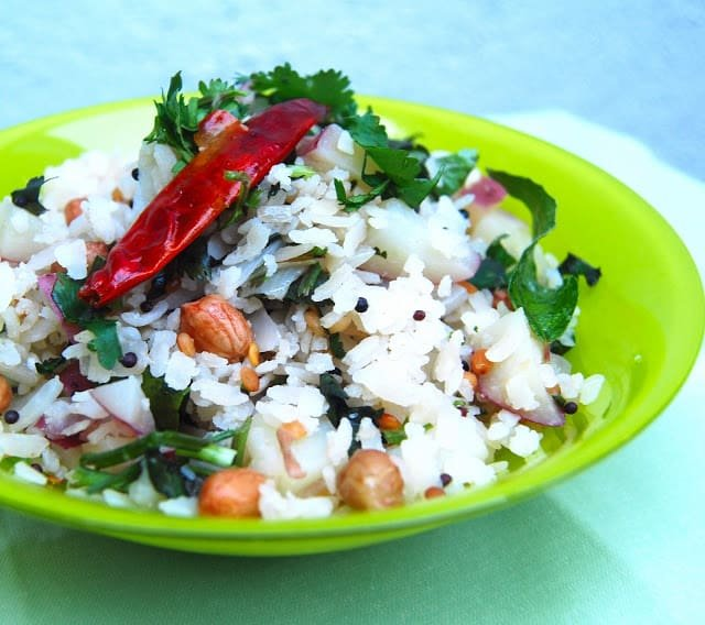 Photo of aval upma with peanuts, mustard seeds, potatoes and cilantro in a green bowl.