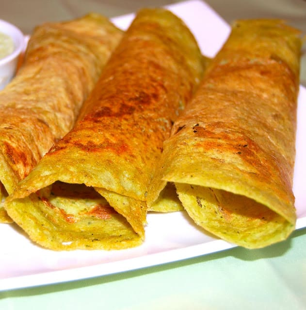 Photo of bean and oats dosas arranged on a white plate.
