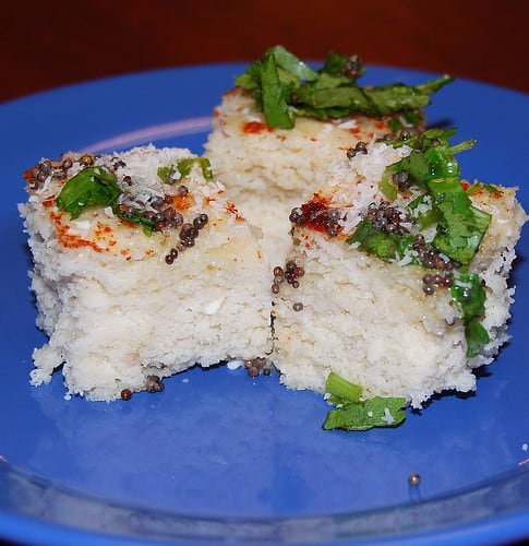 Photo of three pieces of brown rice dhokla with cayenne, mustard seeds and cilantro on a blue plate.