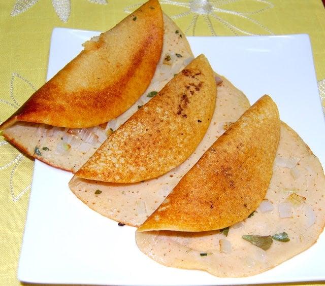 Three uthappams on a white plate.