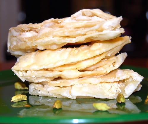 Photo of a stack of chavde or mande on a green plate with cardamom pods scattered around.