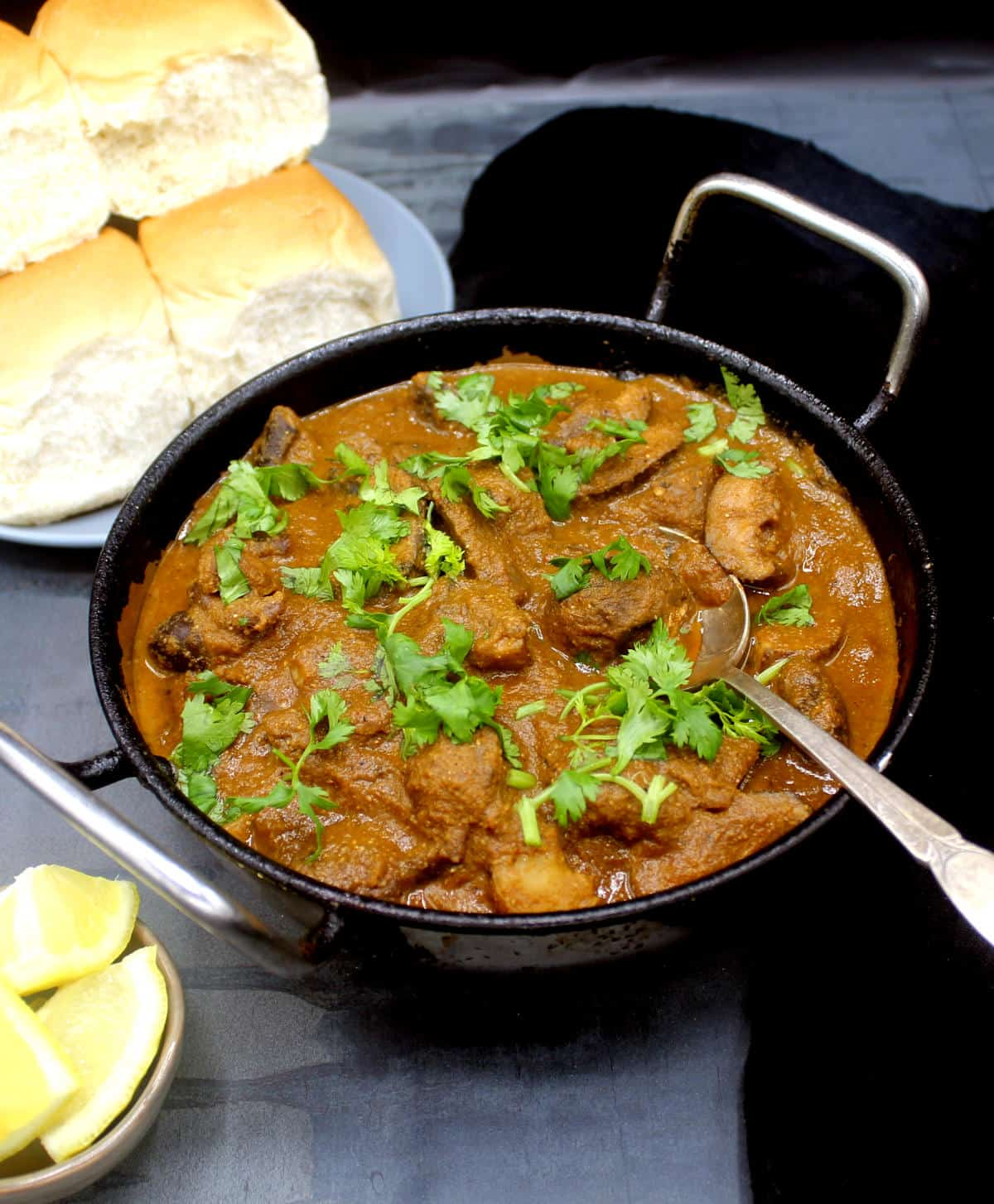 Front photo of my dad's mushroom curry in a karahi with cilantro and a spoon with ladi pav bread rolls and lemon wedges next to it.