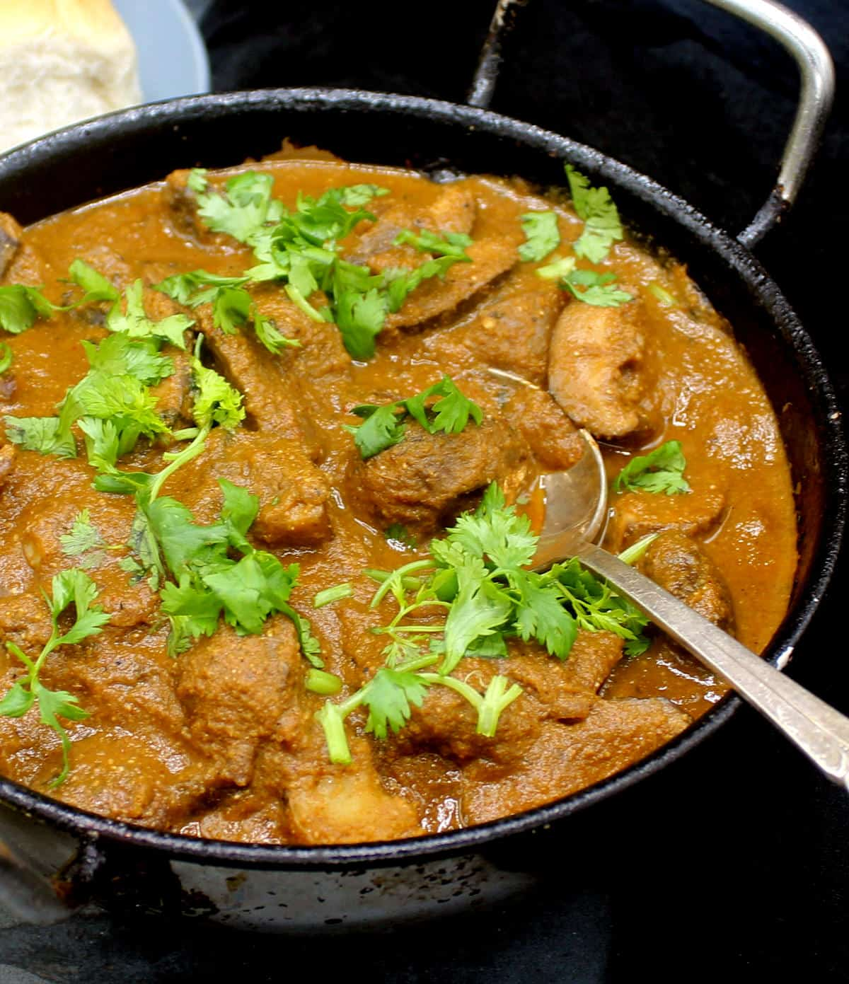 Closeup photo of my dad's not mutton mushroom curry in a karahi with cilantro garnish, mushrooms, potatoes and a spoon.