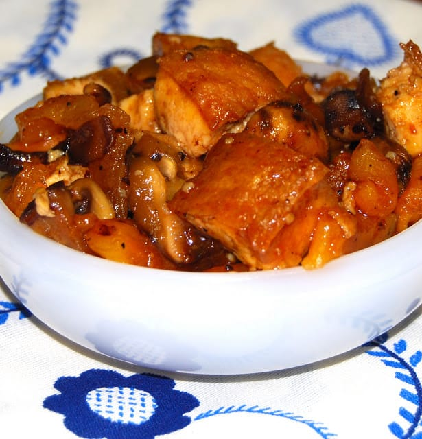 Photo of chewy tofu cubes in a Mexican-inspired chipotle tamarind sauce in a white bowl on a blue and white tablecloth.