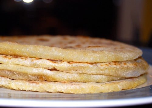 Photo of four puran poli stacked on a plate.
